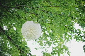 white coffee filter pom hanging at wedding