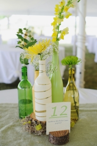 DIY wedding centerpieces :: yellow and green wine bottles and tree stumps